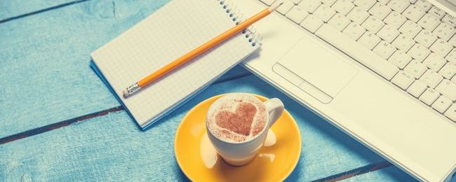 cup of coffee and laptop with note on blue wooden table.